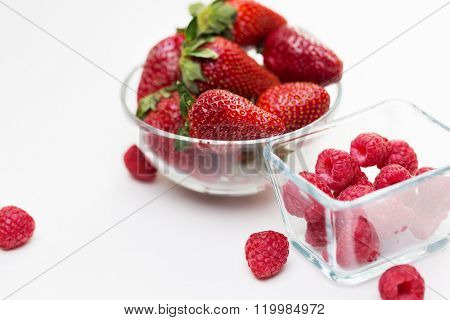 fruits, berries, diet, eco food and objects concept - close up of juicy fresh ripe red strawberries and raspberries in glass bowls over white