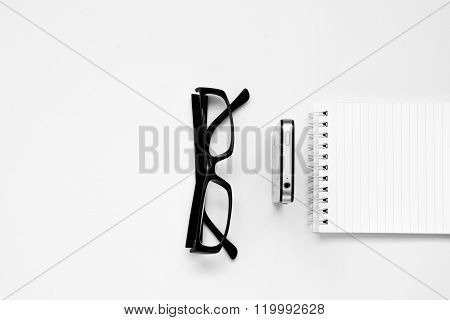 Smartphone, Glasses, and notepad isolated. Office accessories. White background.