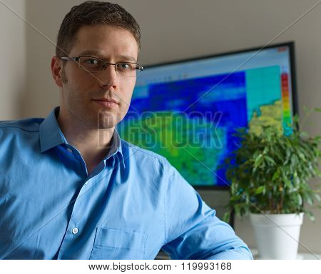 Handsome male meteorologist in glasses on his workplace.