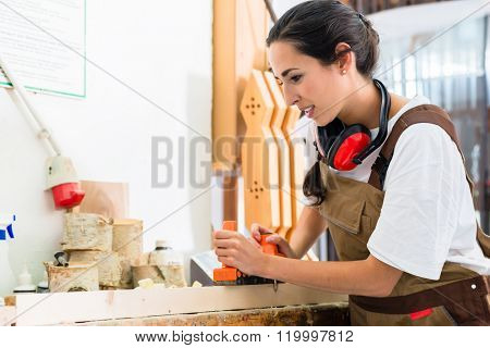 Carpenter woman working with planer in her workshop