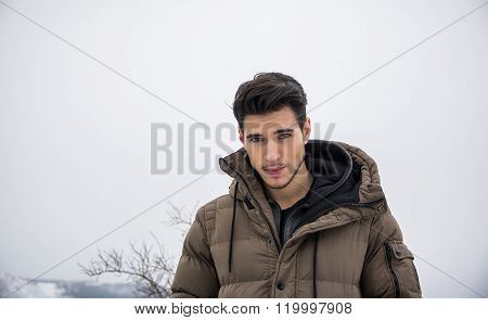 Man in outerwear sitting while looking at camera