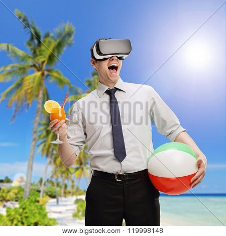 Young businessman visualizing a beach environment using a VR headset and holding a cocktail and a beach ball shot with tilt and shift lens