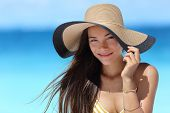 Asian woman wearing fashion straw beach hat for skin care sun protection. Face skincare beauty concept. Beautiful Chinese Caucasian mixed race young adult girl portrait on summer vacation travel. poster