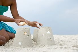 Mother and child putting shells on sandcastles