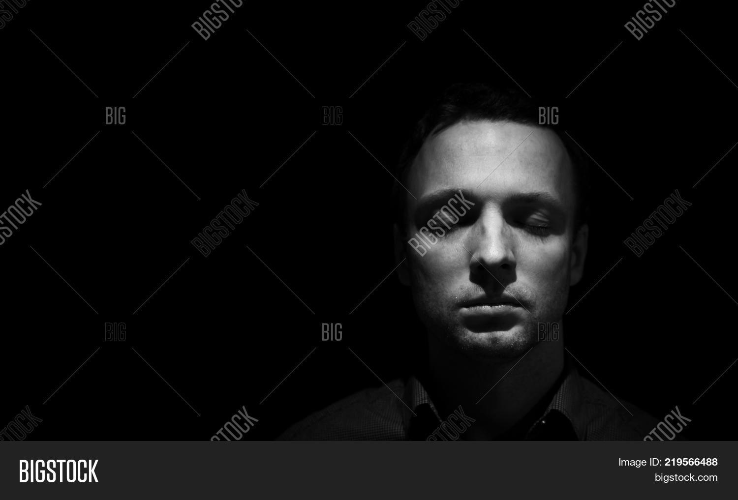 Closeup studio face portrait of young adult european man with closed eyes isolated over black background