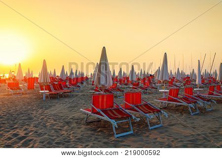 Sunbeds on the beach at sunrise in Rimini Italy
