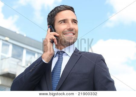 Property salesman stood outdoors with mobile telephone