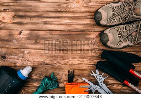 Top view of equipment for hiking and travel on wooden table with empty space in the middle. Items include trekking pole, shoes, multi tool, hermetic bag, rope, water bottle