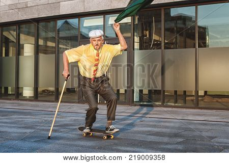 Playful grandfather is rolling on a skateboard in his hand a jacket with which he is waving.