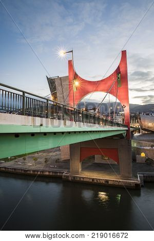 Bilbao, Spain - January 29, 2016: evening view of La Salve Bridge with its Arcos Rojos or Red arches, sculpture designed by French Artist Daniel Buren and inaugurated in 1997