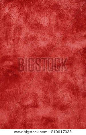 Grunge burgundy red vivid uneven old aged daub plaster wall texture background with stains and paint strokes close up