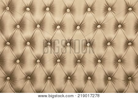 Beige capitone textile background retro Chesterfield style checkered soft tufted fabric furniture diamond pattern decoration with buttons close up