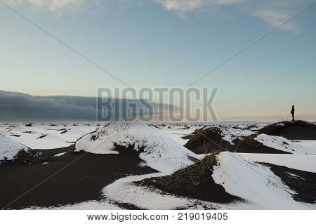 Dark clouds build in the distance over snow covered black sand dunes near Vik Iceland on the south coast of the island. A person is standing on one of the dunes watching the approaching storm.