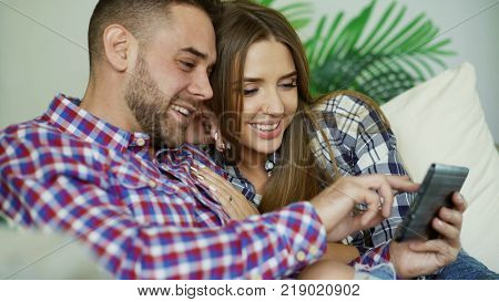 Young attractive couple using tablet computer for surfing online and chatting sit on couch in living room at home