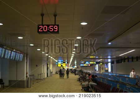 digital clock hanging on the ceiling to display the time at 20.59 pm for passenger at arrival and departure in the airport with blurred terminal background.