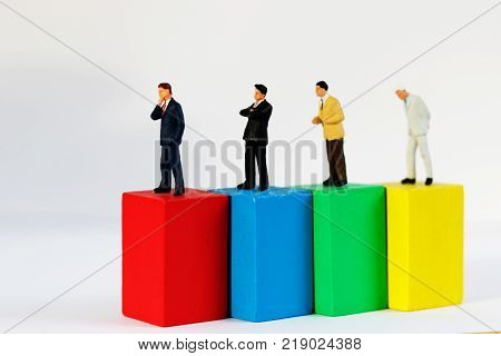 Miniature people: Businessman standing on top wooden block. Business management concept