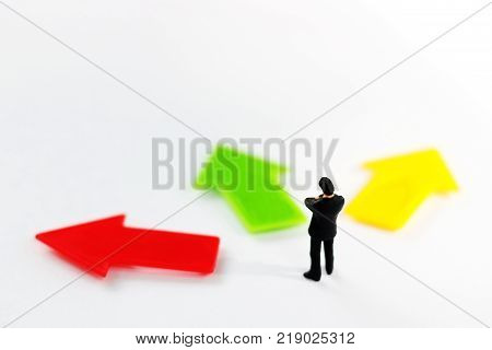 Miniature people standing whit arrow pathway choice. Business decision concept.