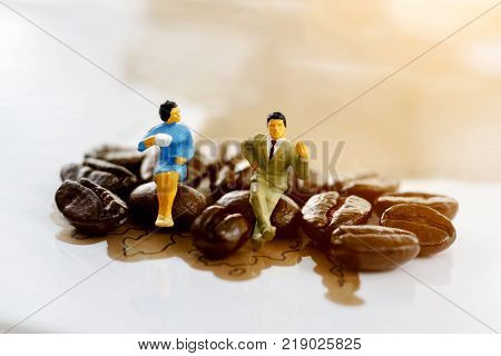 Miniature people sitting on coffee bean Coffee time concept.