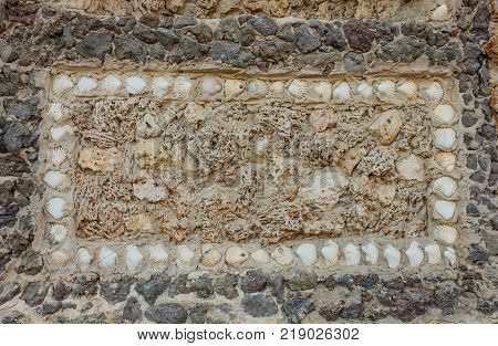 geometric composition with shells and marine sponges /original rectangle of seashells and marine sponges on a stone wall