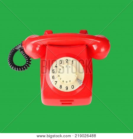 Beautiful red vintage phone on a green background