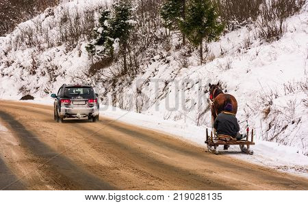Volovets Ukraine - December 16 2016: traffic in mountainous rural area in winter. cart with one horse outscored by SUV on snowy countryside road