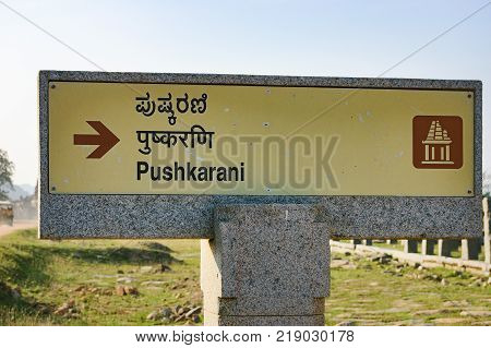 Hampi, India - November 20, 2012: Signpost for tourists about Pushkarani market complex near temple tank on the way to the Vitthala temple, Hampi, Karnataka, India.
