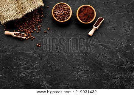 Coffee concept. Roasted beans and ground coffee an bowls and scoop on black background top view.