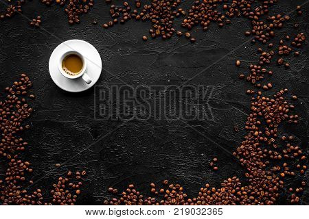 Cup of milky coffee on black table top view copyspace. Coffee background
