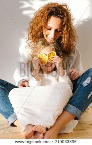 Smiling happy mother with curly hair sits crossed legs on floor with her daughter who has fun and covers eyes with two pieces of oranges, enjoy togetherness, have fun at home. Family concept.