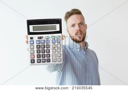 Portrait of upset young man unfocused with calculator in focus. Book-keeper demonstrating loss. Finance and disadvantage concept.