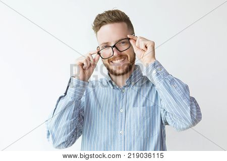 Portrait of attractive laughing young man wearing glasses incorrectly. Work balance or self irony concept.