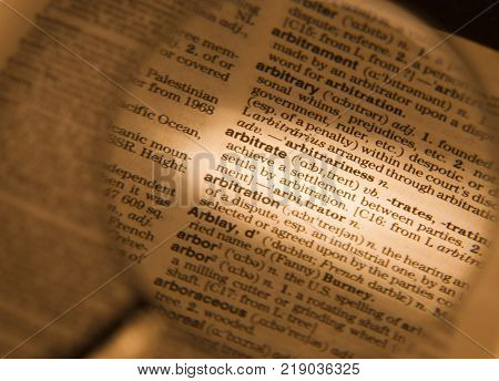 CLECKHEATON, WEST YORKSHIRE, UK:MAGNIFYING GLASS ON DICTIONARY PAGE SHOWING DEFINITION OF THE WORD ARBITRATE, CIRCA 2005, CLECKHEATON, WEST YORKSHIRE, UK