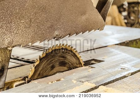 Disc electric circular saw on the stand frame. Sawing machine in working carpentry workshop. Mechanized woodworking carpenter tool close-up. Toothed saw blade. Limeted depth of field.
