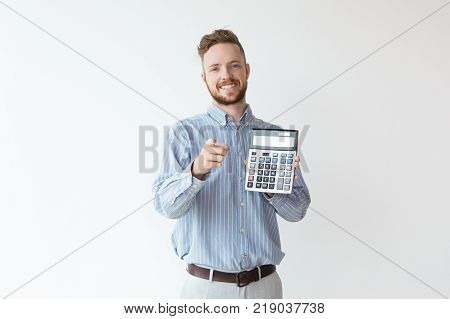 Portrait of attractive smiling young manager holding calculator and pointing finger at camera. Credit manager proving favorable terms with calculating. Finance concept.