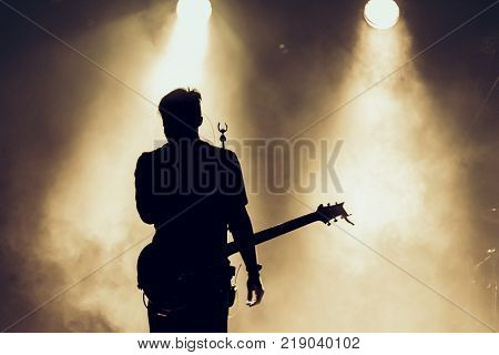 Rock band performs on stage. Guitarist plays solo. silhouette of guitar player in action on stage behind lights