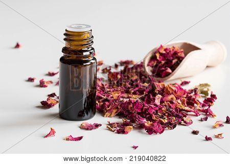 A dark bottle of rose essential oil with dried rose petals on a white background