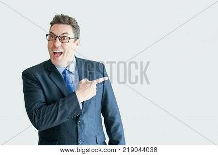 Closeup portrait of happy middle-aged business man looking at camera and pointing finger at empty space. Isolated front view on white background. Recommendation concept.