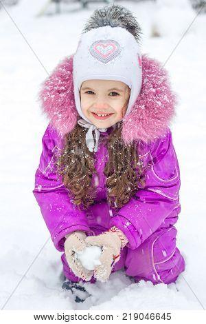 Little kid girl playing snowballs on winter morning