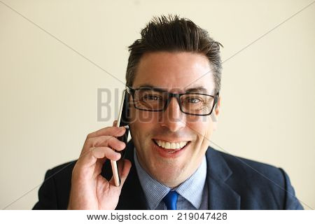 Cheerful optimistic male manager using mobile phone and looking at camera. Portrait of happy middle-aged businessman having phone conversation. Communication concept