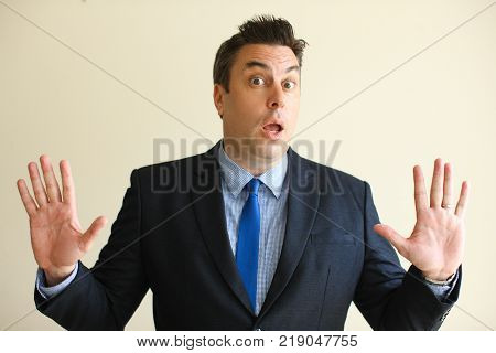 Confused businessman putting hands up and looking at camera. Puzzled middle-aged male executive turning in to police or making stop gesture. Business crime concept