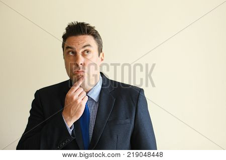 Pensive businessman elaborating idea and rubbing chin. Curious handsome middle-aged male employee thinking of project. Enterprise concept