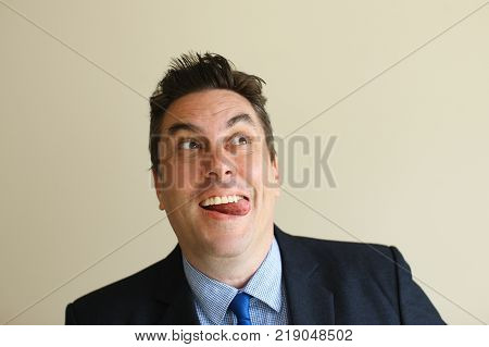 Playful funny businessman sticking tongue out and looking up. Positive handsome middle-aged businessman leading unfair game. Prankster concept