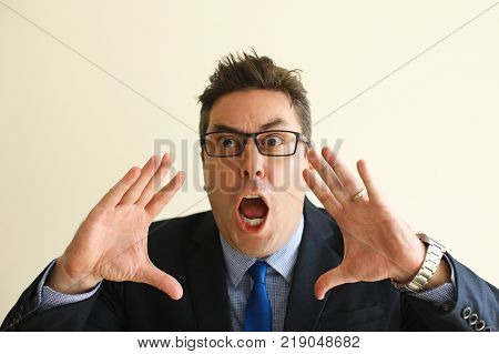 Scared middle-aged businessman screaming at camera. Emotional sales manager with open mouth feeling fear or shock. Negative emotions concept