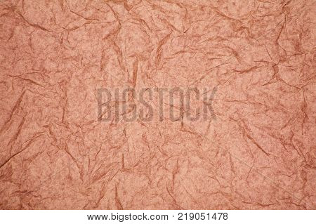 ABSTRACT RANDOM BACKGROUND OF CREASED CRUMPLED PALE PINK TISSUE PAPER