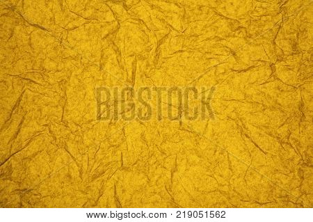 ABSTRACT RANDOM BACKGROUND OF CREASED CRUMPLED AMBER TISSUE PAPER