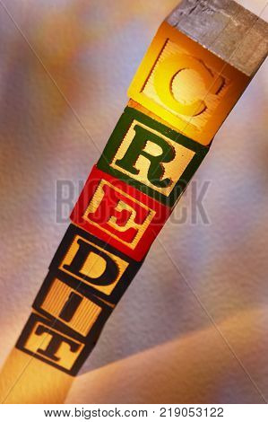 STACK OF WOODEN TOY BUILDING BLOCKS SPELLING THE WORD CREDIT