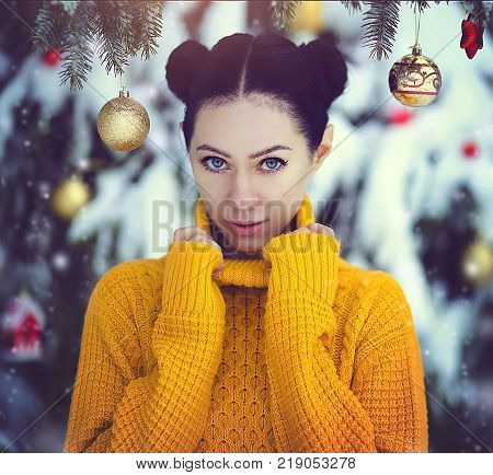 Beautiful girl with blue eyes in a yellow sweater under a snow-covered Christmas tree with Christmas toys. A girl in fairy-tale New Year's decorations. Magic winter forest. Creative colors and Artistic processing.