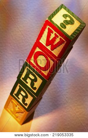 STACK OF WOODEN TOY BUILDING BLOCKS SPELLING THE WORD WORRY
