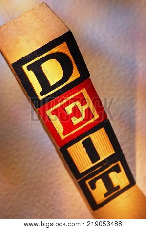STACK OF WOODEN TOY BUILDING BLOCKS SPELLING THE WORD DIET