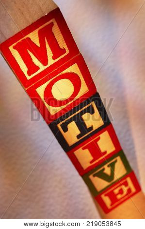 STACK OF WOODEN TOY BUILDING BLOCKS SPELLING THE WORD MOTIVE